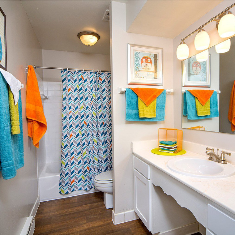 White Bathroom with Orange, Green, and Blue towels